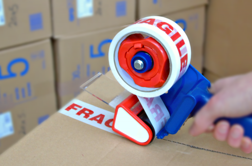 Blue & Red Tape Gun With Fragile Printed Tape Closing A Cardboard Box